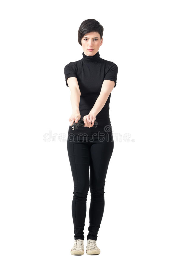 Tough woman secret agent in black clothes cocking gun. royalty free stock image