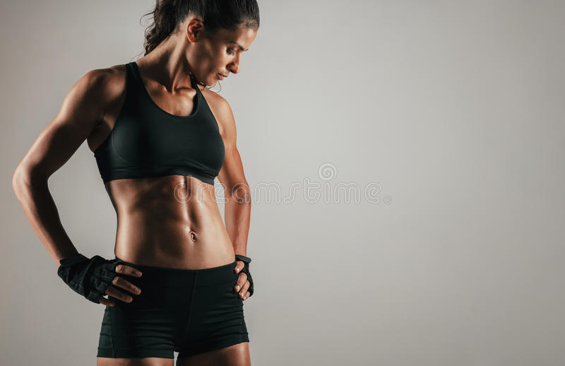 Tough woman with tight abdominal muscles. Tough woman with gloved hands on hips featuring tight abdominal muscles over gray background with copy space stock photography