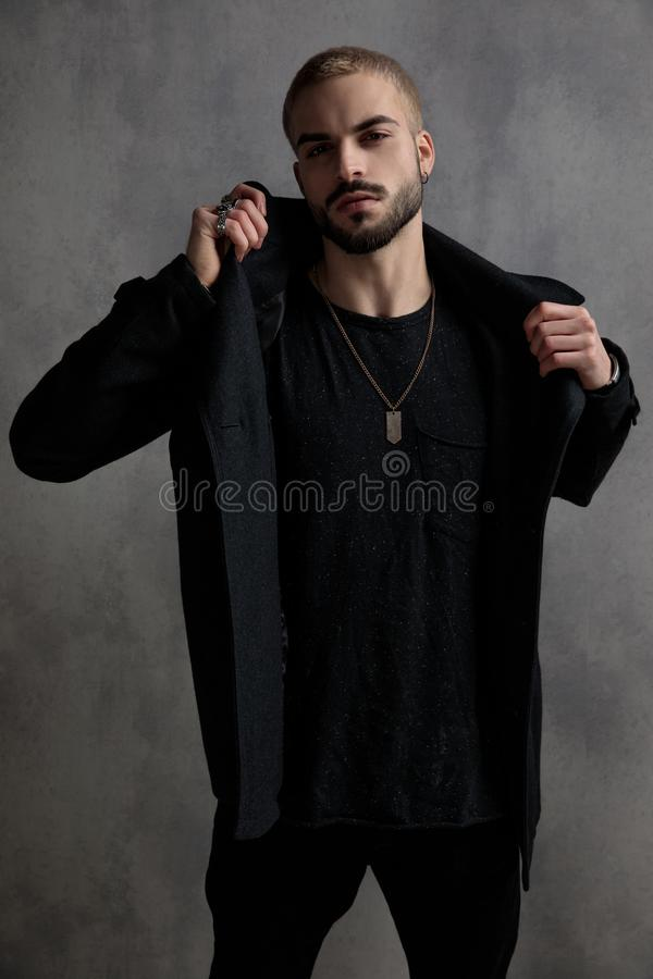 Free Tough Young Man Adjusting His Black Long Coat Stock Photos - 161057863