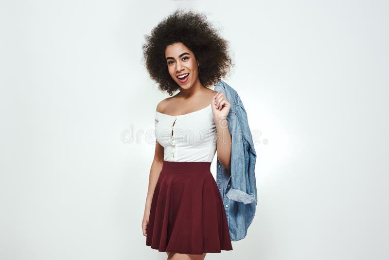 Toujours dans le style La jeune et mignonne femme afro-américaine avec les cheveux bouclés earing les vêtements sport tient la ch photos stock
