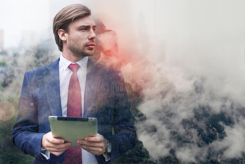 Toujours en ligne Homme d'affaires sérieux et sûr tenant son comprimé numérique tout en se tenant contre des montagnes brumeuses photo libre de droits