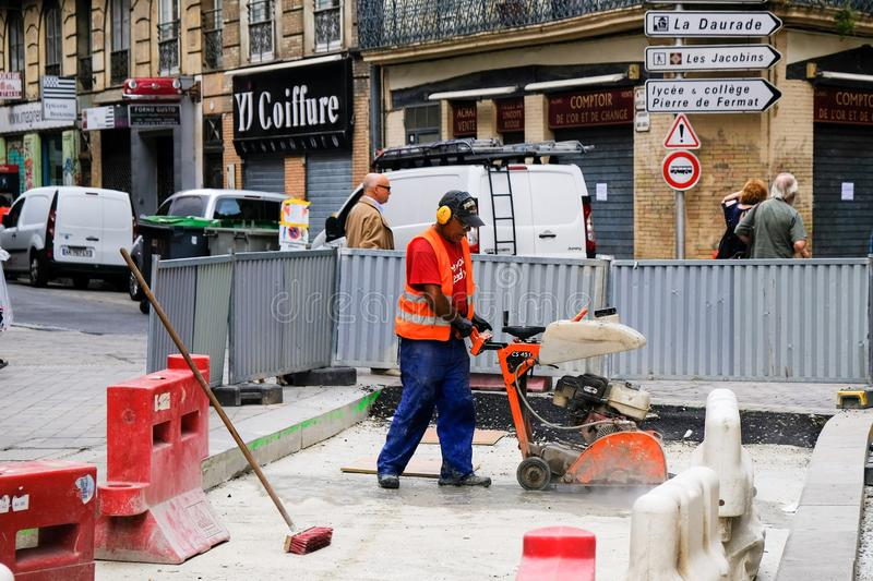 TOULOUSE, FRANCE - AUGUST 10, 2018 - Road worker in orange uniform cutting concrete surface with hydraulic driven angle grinder on royalty free stock photo
