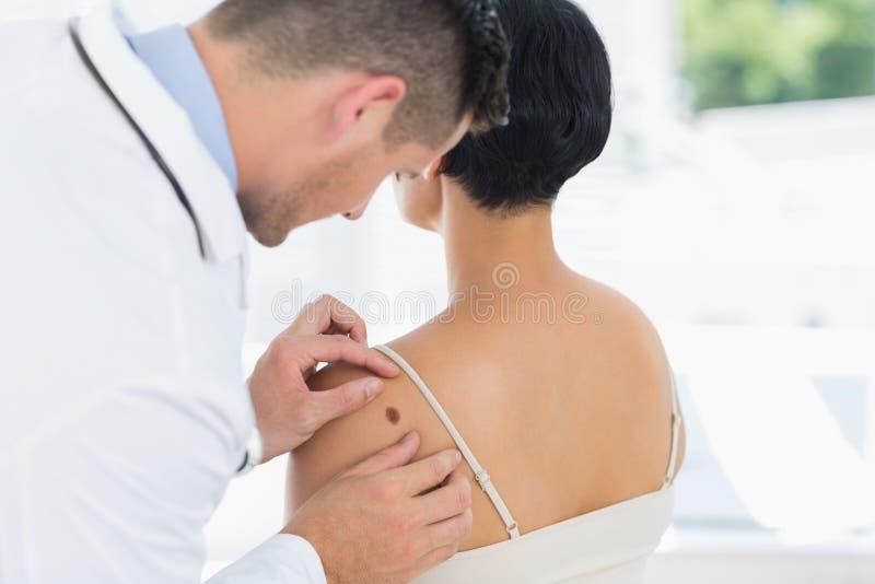 A toupeira de exame do doutor suporta sobre da mulher imagem de stock