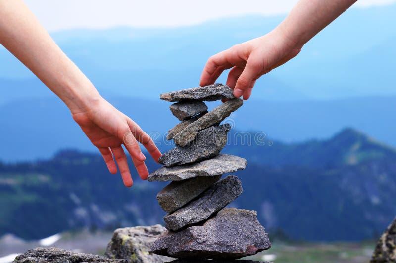 Tour équilibrée de roche de main, fond de montagne, concept de travail d'équipe photos libres de droits