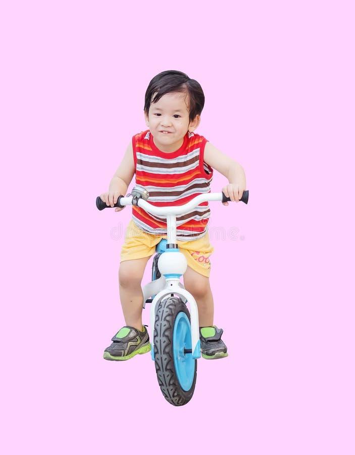 Tour asiatique mignon d'enfant de plan rapproché une bicyclette d'isolement sur le fond rose images stock