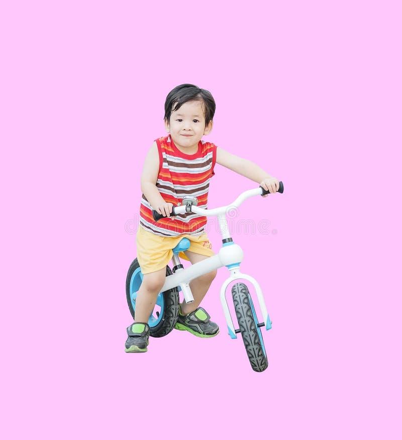 Tour asiatique mignon d'enfant de plan rapproché une bicyclette d'isolement sur le fond rose photographie stock