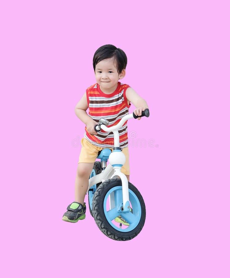 Tour asiatique mignon d'enfant de plan rapproch? une bicyclette d'isolement sur le fond rose photos stock