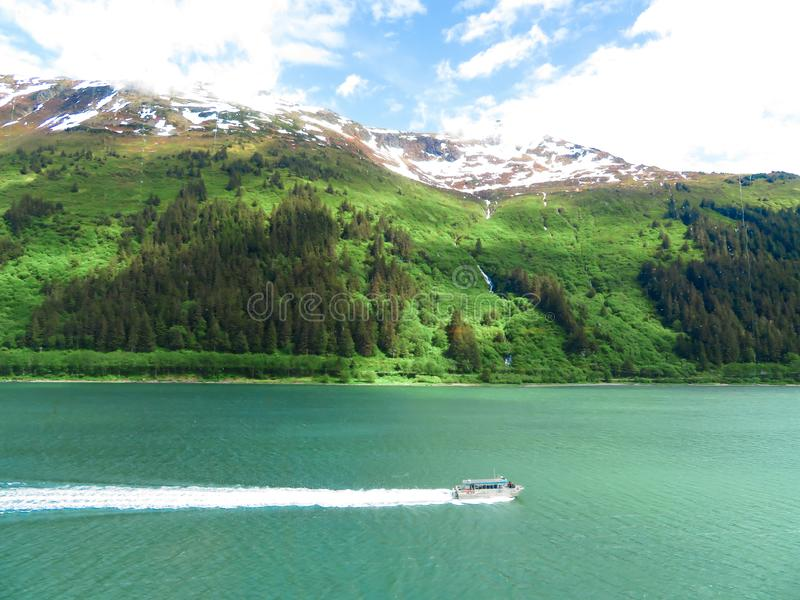 Tour boat in Alaska heading to pick up it`s passengers from a cruise ship stock photo
