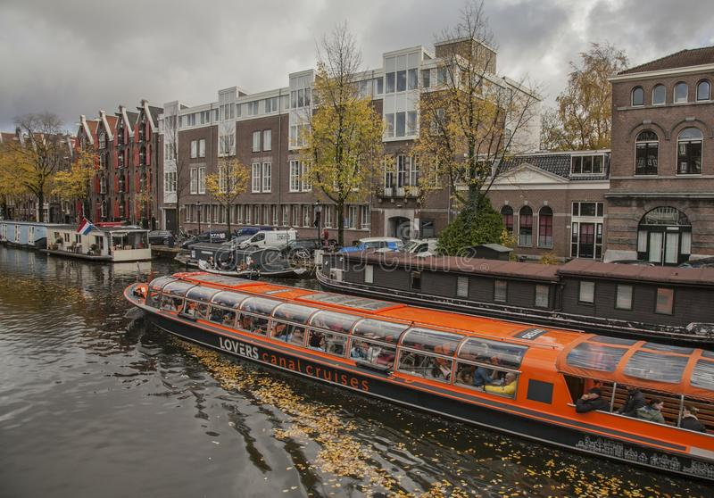 Tour boat on a canal; a cloudy day in Amsterdam. stock photography
