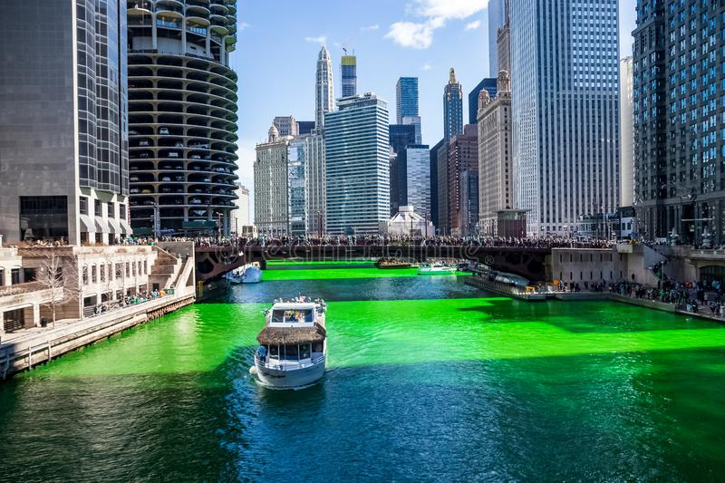 Tour boat crosses a dyed green Chicago River, which is surrounded by crowds royalty free stock photos