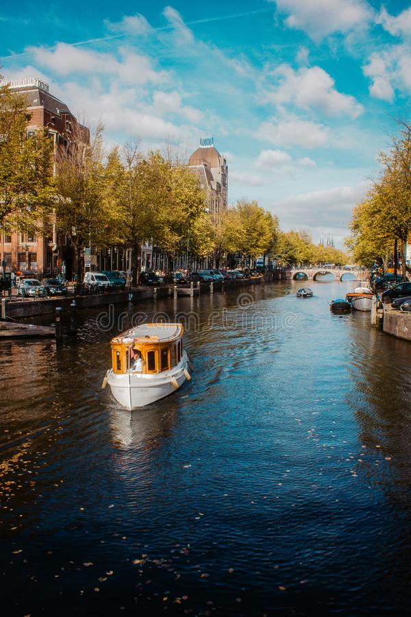 Tour Boat Cruising on one of the famous Amsterdam canals on the beautiful, sunny Autumn day. Amsterdam, Netherlands - October 18, 2018: Tour Boat Cruising on stock photo