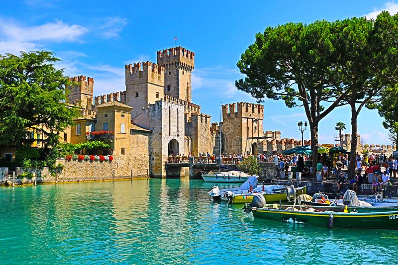 Tour boats in Lake Garda and Scaligero Castle Sirmione town Italy. Tour boats moored at pier in front of Scaligero Castle and yellow luxury hotel buildings in royalty free stock photography