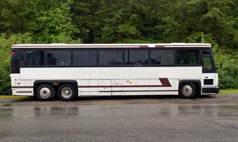 Tour Charter Bus. Side view of parked white tour charter bus on a rainy day royalty free stock photos