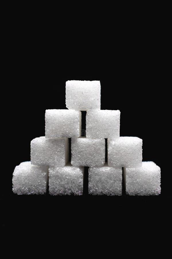 Tour construite hors des cubes blancs en sucre sur le fond noir d'isolement photo stock