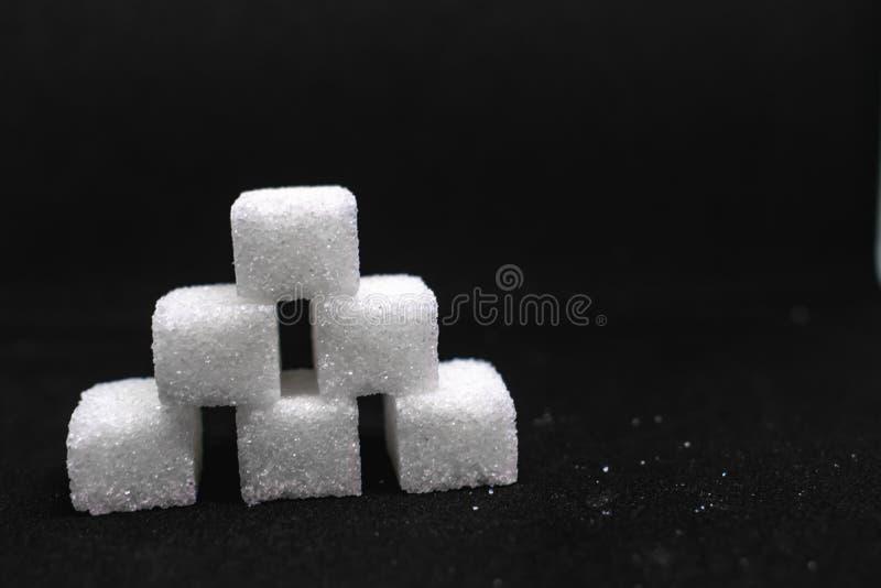 Tour construite hors des cubes blancs en sucre sur le fond noir d'isolement photos libres de droits