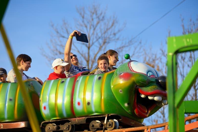 Tour d'adultes et d'enfants sur les montagnes russes russes image stock