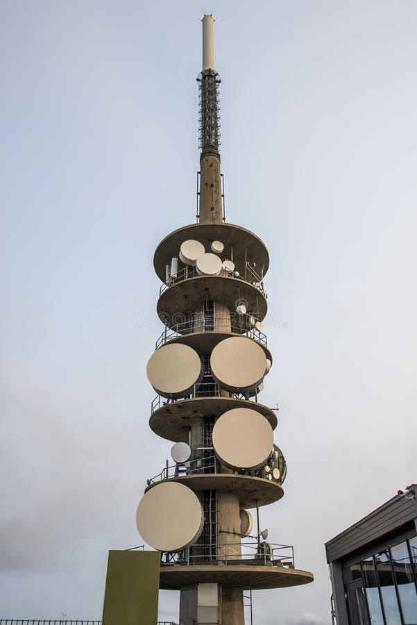 Tour d'antenne lumineuse avec beaucoup d'équipement contre un ciel bleu photographie stock libre de droits