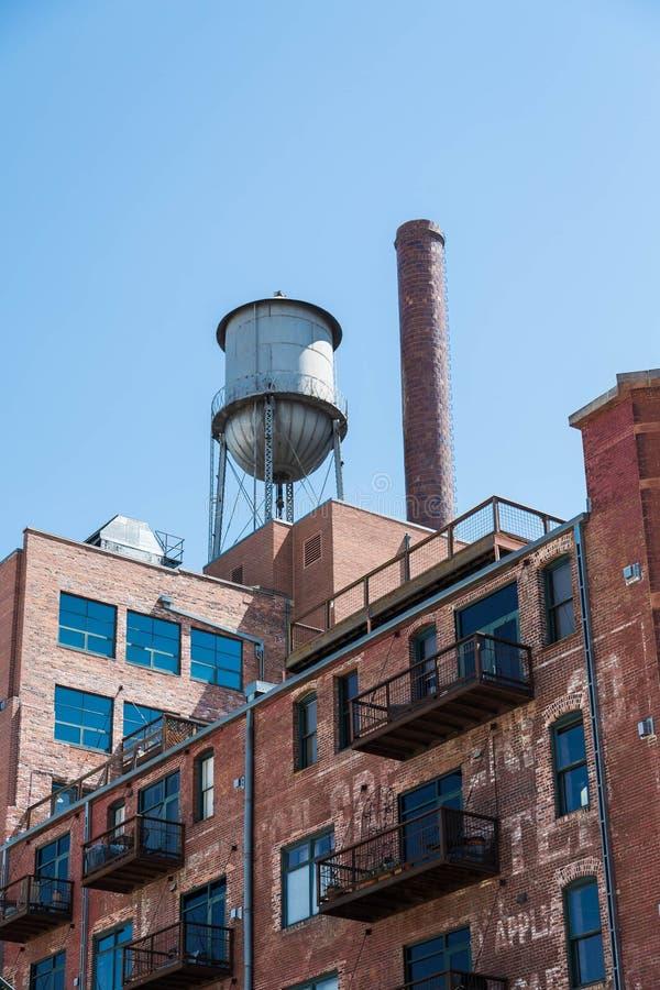 Tour d'eau sur le vieil immeuble de brique avec des balcons en métal photographie stock