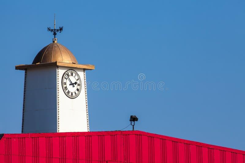 Tour d'horloge vibrante de pilier de bord de la mer avec le weathervane photos stock