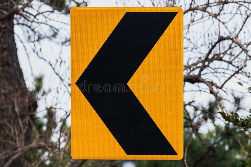 Tour dangereux laissé, panneau routier noir jaune photo stock