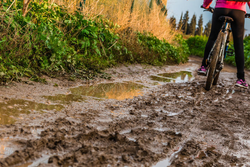 Tour de bicyclette par le chemin de terre boueux photo libre de droits