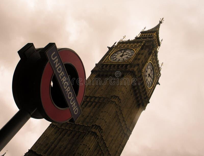 Tour de Big Ben et le signe de Métro de Londres contre un ciel nuageux photos stock