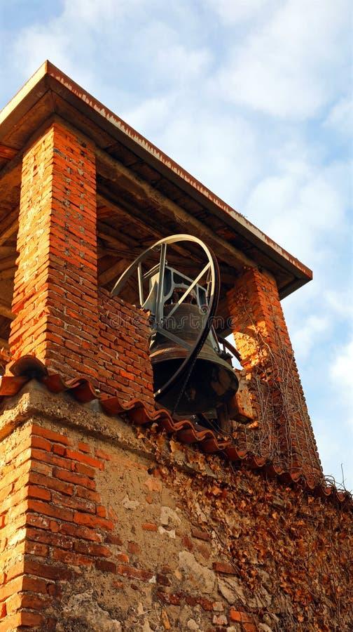 Tour de cloche médiévale antique de brique avec la cloche en bronze et le ciel bleu image libre de droits