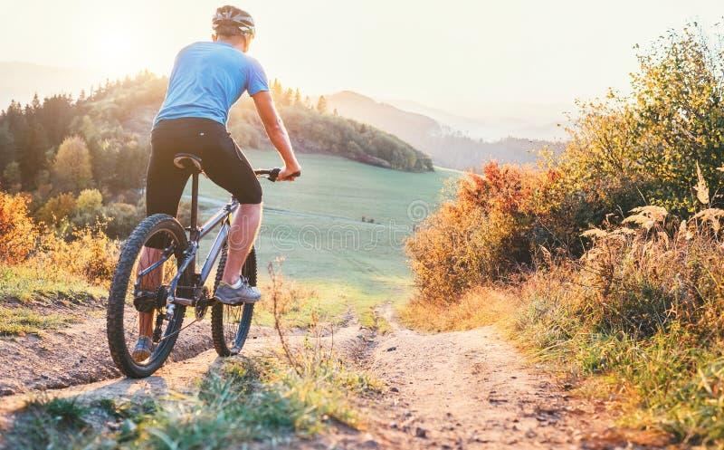 Tour de cycliste de montagne vers le bas de colline Escroquerie active et de sport de loisirs image libre de droits