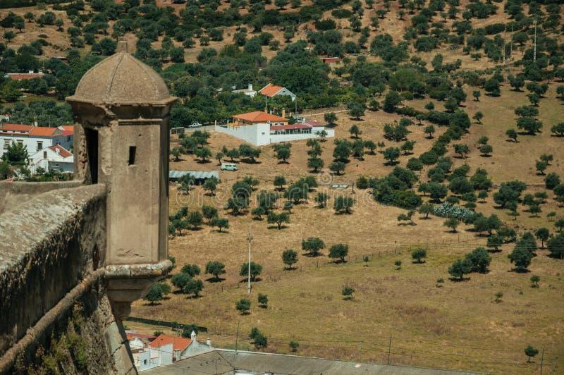 Tour de guet sur un mur de forteresse devant des fermes et des arbres image stock
