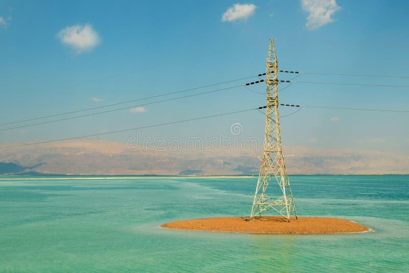 Tour de l'électricité sur un remblai arénacé contre un ciel bleu avec des nuages, une tour avec des fils en mer morte, photo libre de droits