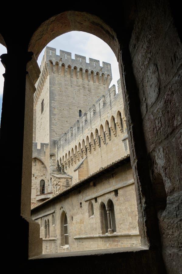 Tour de la Campane through arched window. Tour de la Campane seen through an arched window at the Palais des Papes, Avignon, France royalty free stock photography