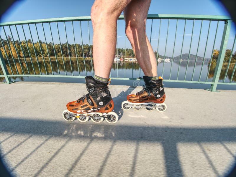 Tour de patineur de rouleau en parc Jambes de garçon dans des lames dures intégrées de bottes de coquille photo libre de droits