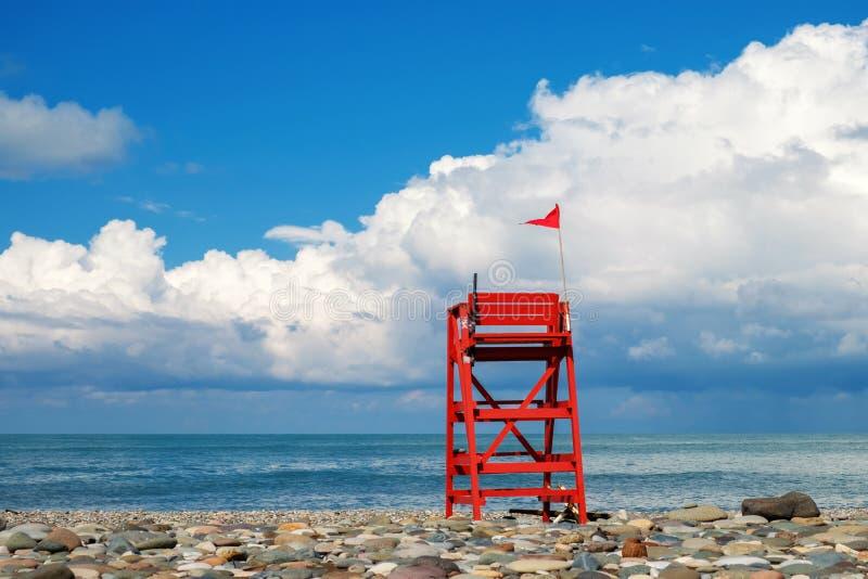 Tour de sauvetage rouge sur la plage rocheuse vide avec fond bleu ciel nuageux images libres de droits