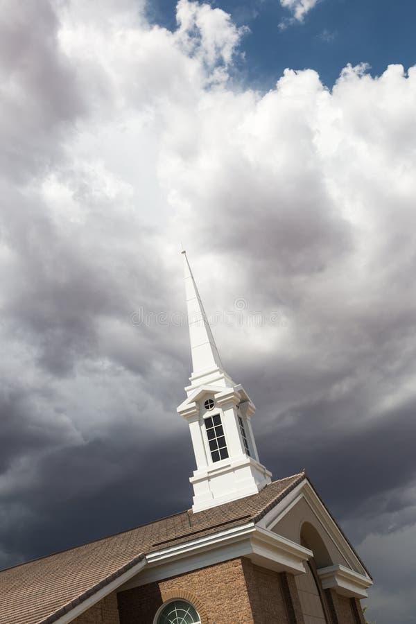 Tour de Steeple d'église au-dessous des nuages orageux sinistres d'orage photographie stock