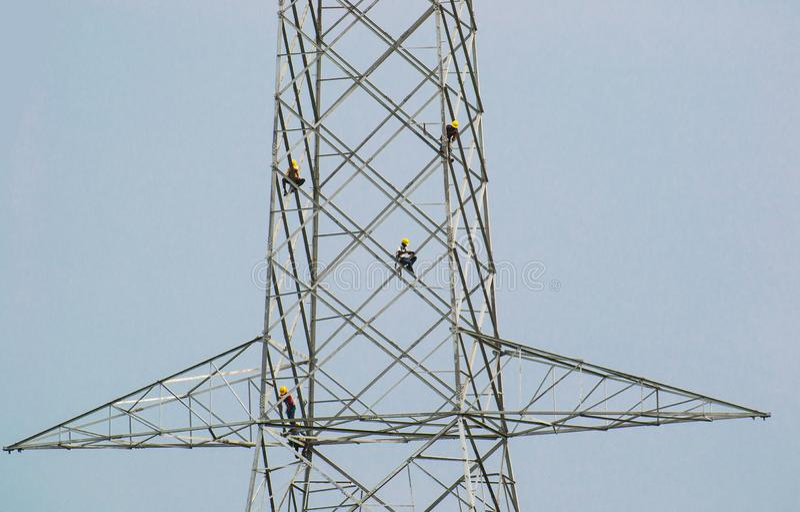 Tour de transmission de l'électricité avec des travailleurs photos stock