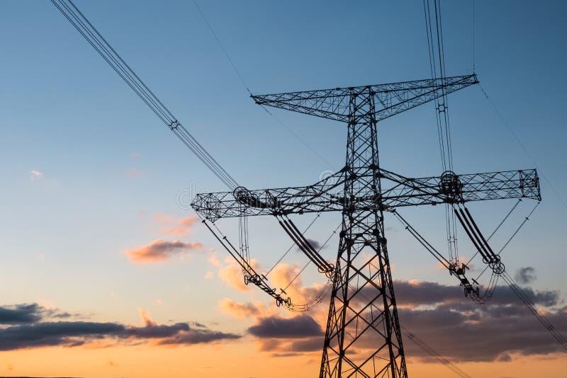 Tour de transport d'énergie avec la lueur de coucher du soleil image libre de droits