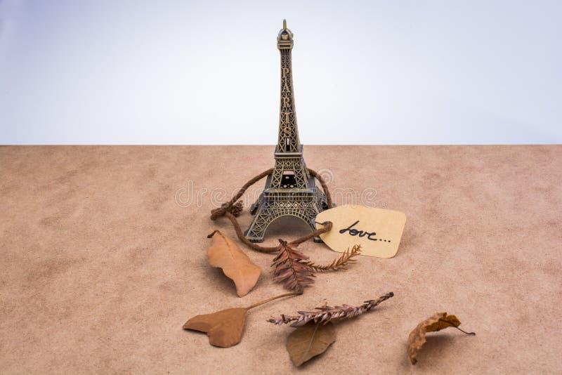 Tour Eiffel et sèchent des feuilles sur le fond brun images stock