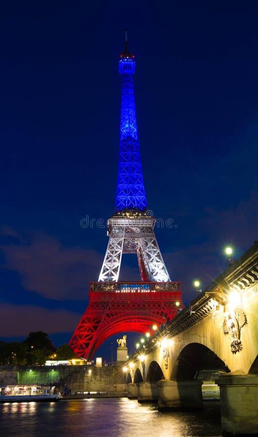 Tour Eiffel s'est allumé avec les couleurs du drapeau national français photo stock