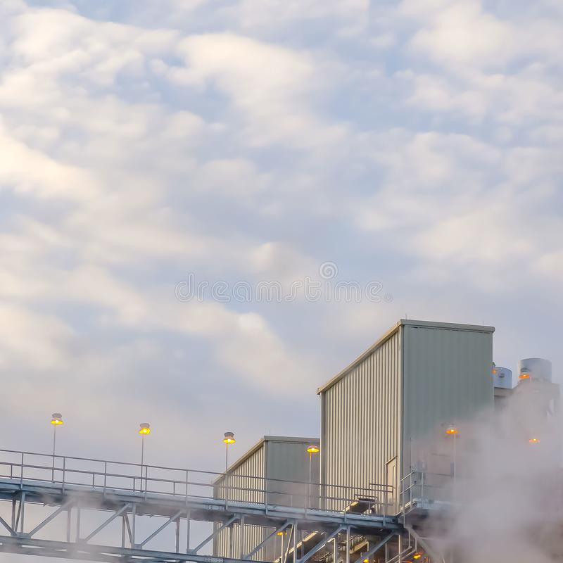 Tour et bâtiments carrés clairs d'une centrale avec la vapeur se levant dans le ciel de vallée de l'Utah images libres de droits