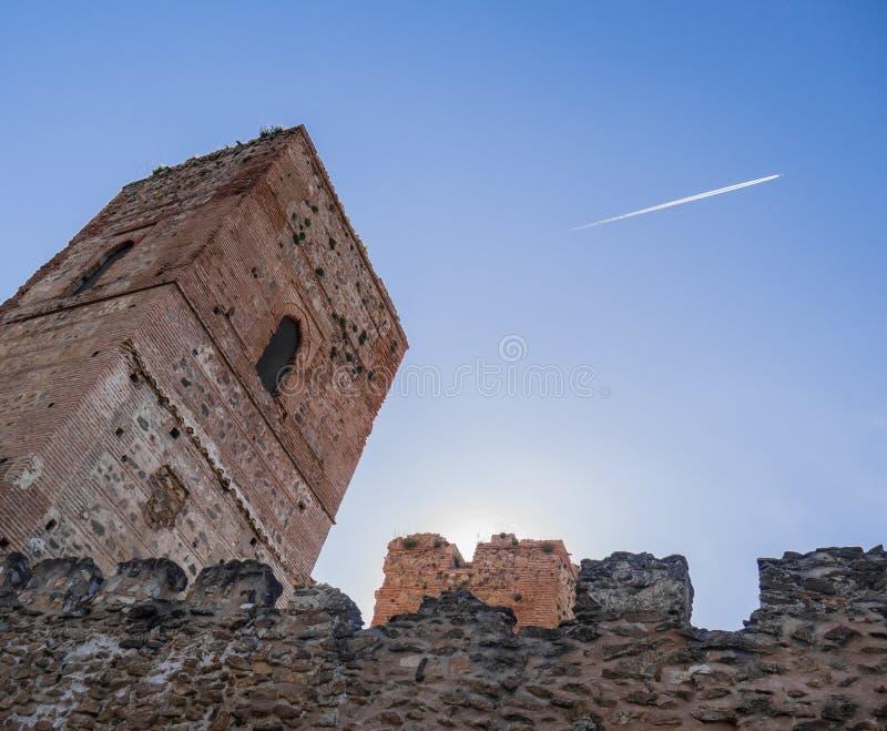 Tour et mur de Buitrago De Lozoya au coucher du soleil avec un ciel bleu et une traînée blanche d'avion photos stock