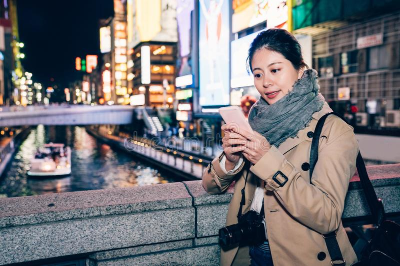 Tour guide boat on the river sightseeing. Asian woman traveler texting message online standing on the bridge above the canal in dotonbori osaka japan. tour guide stock photo