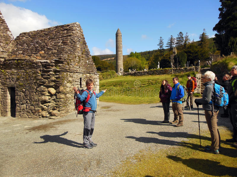 Tour Guide Ireland. An Irish archeologist conducts a guided history tour of an early medieval monastic settlement in Glendalough located in County Wicklow stock images