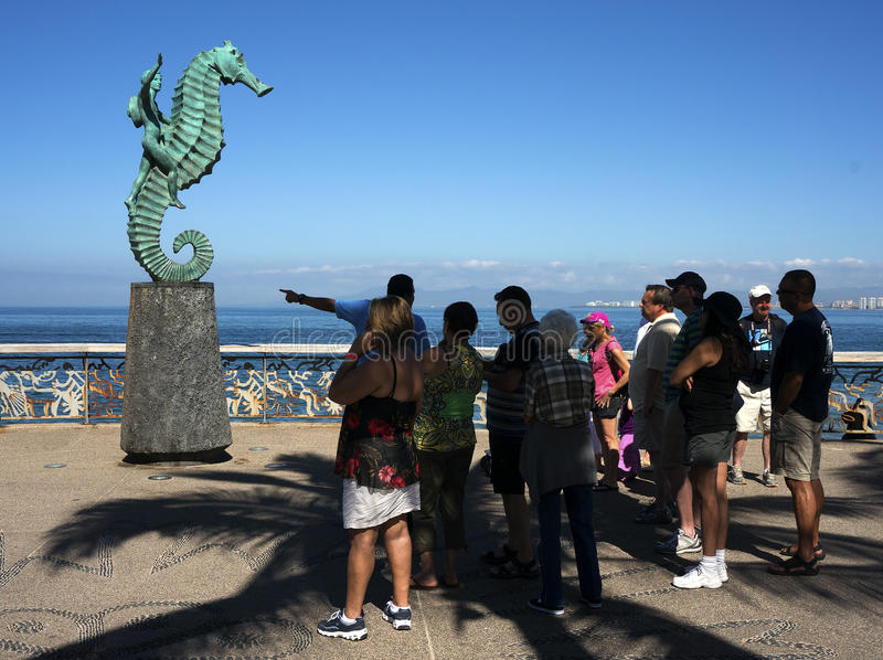 Tour Guide And The Sea Horse Puerto Vallarta Mexico. A tour guide speaks to a crowd of tourists in front of The Sea Horse on the Malecon in Puerto Vallarta stock photo