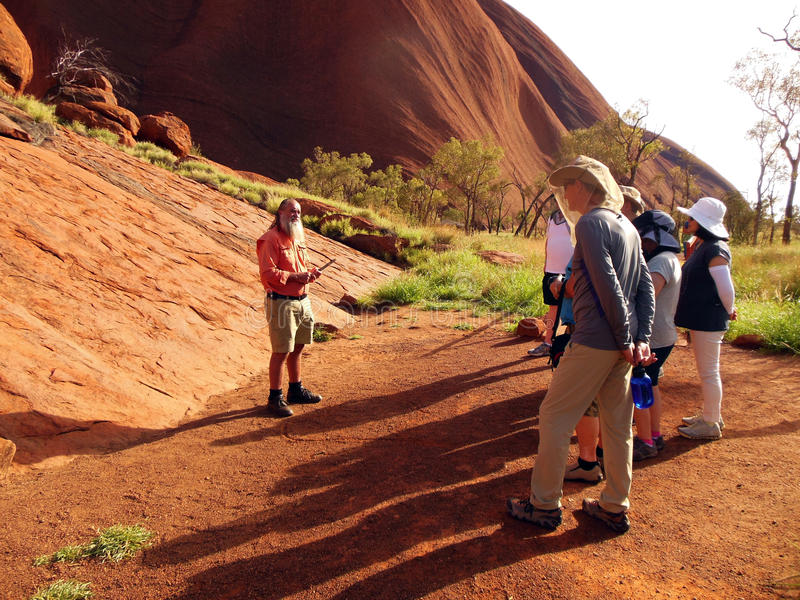 Tour Guide Uluru, Australia. An Aboriginal guide conducts a tour for visitors to Uluru located in the center of Australia. He explains the ancient history and royalty free stock image