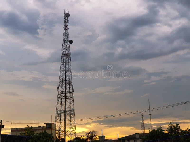 Tour hertzienne avec le nuage et la lumière orange dans la soirée avec la station thermale de copie photo libre de droits