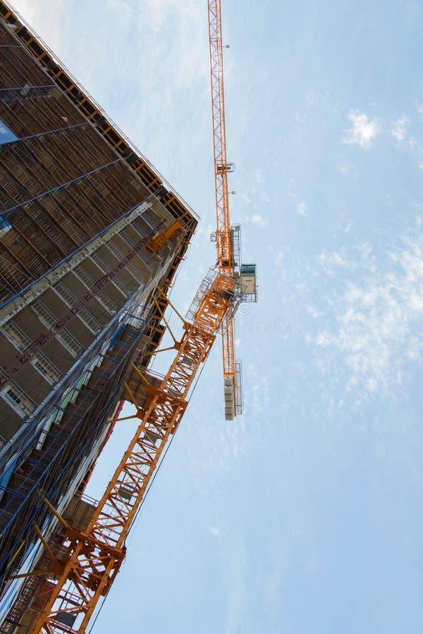Tour jaune de grue de construction et bâtiment inachevé avec le ciel bleu image libre de droits