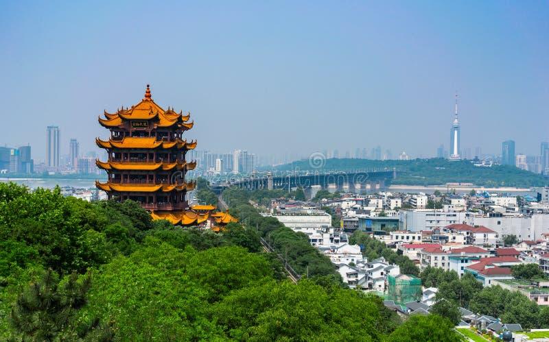 Tour jaune de grue et vue scénique de grand pont de Wuhan le Yang Tsé Kiang dedans photos stock
