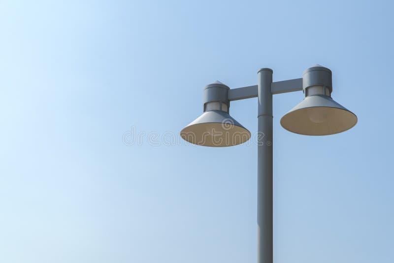 Tour légère et lampe noire avec le fond lumineux de ciel bleu image libre de droits