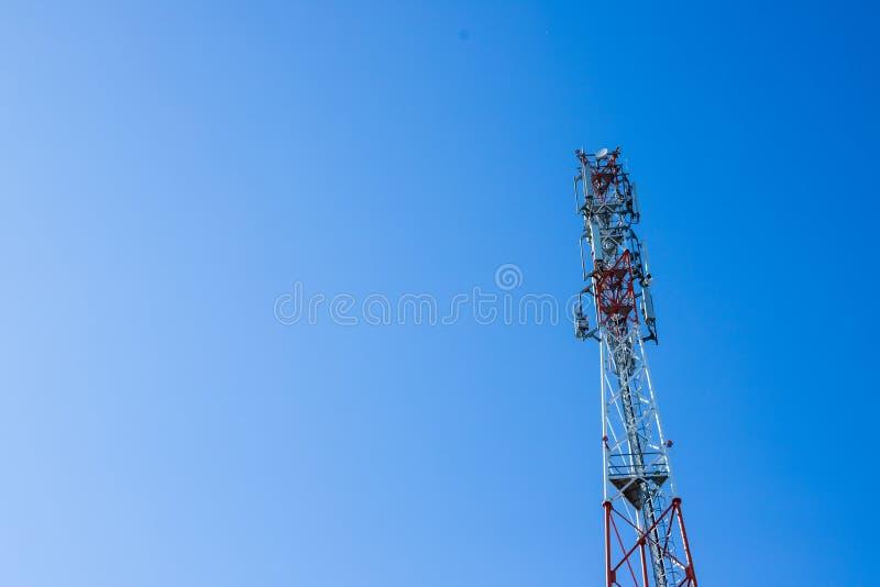 Tour rouge et blanche des transmissions avec avec beaucoup de différentes antennes sous le ciel clair Tour de signal de télécom photographie stock libre de droits