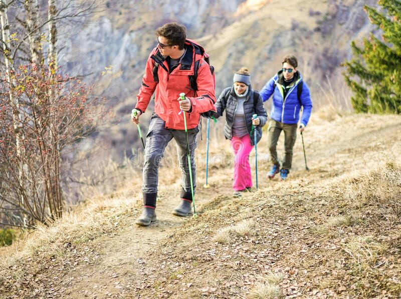 Tour scout guide bringing young couple for trekking excursion - People hiking high mountain in france - Survival,travel and. Adventure concept - Focus on left royalty free stock photography
